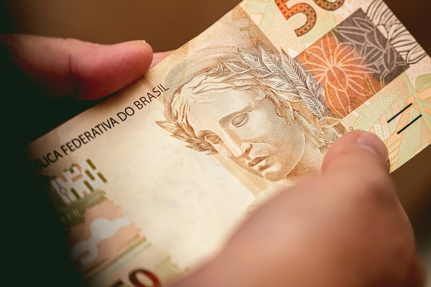 A woman holding in her hands a 50 bill of brazilian money which is the brazilian real