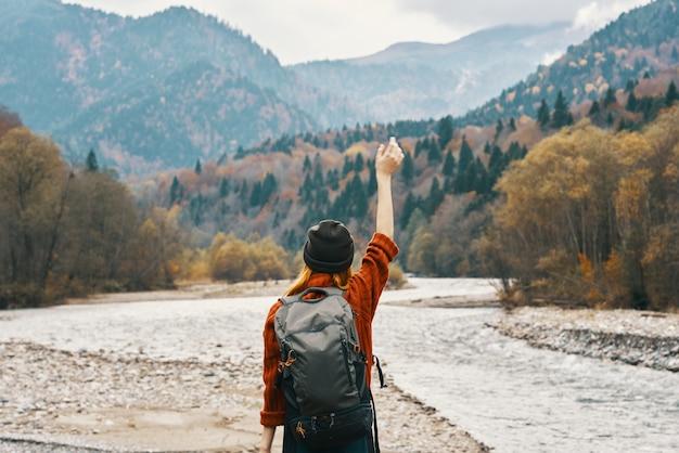 川の旅の近くの秋の屋外の山で彼女の頭の上に彼女の手を保持している女性