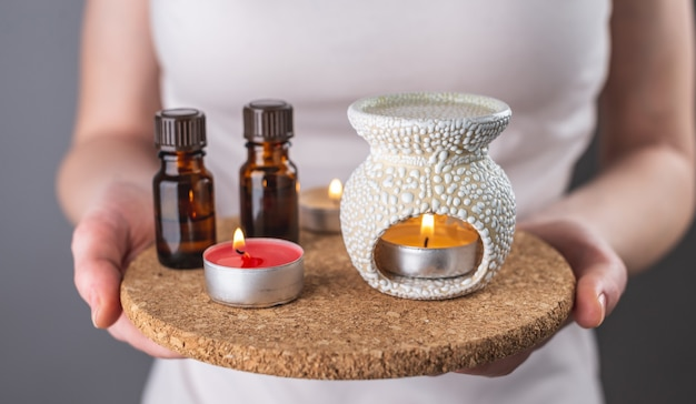 Woman holding in her hands a set for aromatherapy