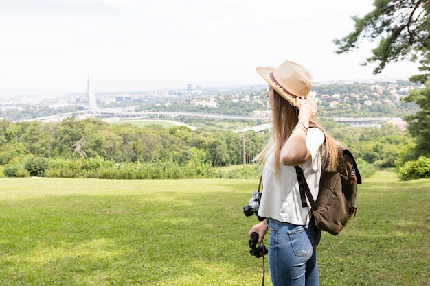 Woman holding her hat and looking away