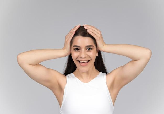 Женщина держит голову и улыбается