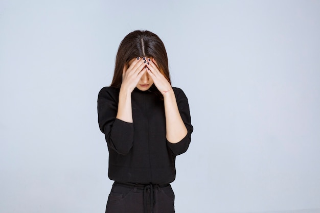Woman holding her head as she is tired or has headache.