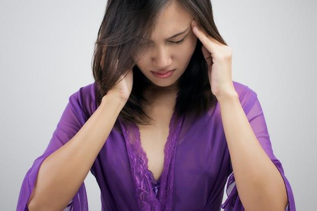 Женщина держит голову руками, потому что болит голова