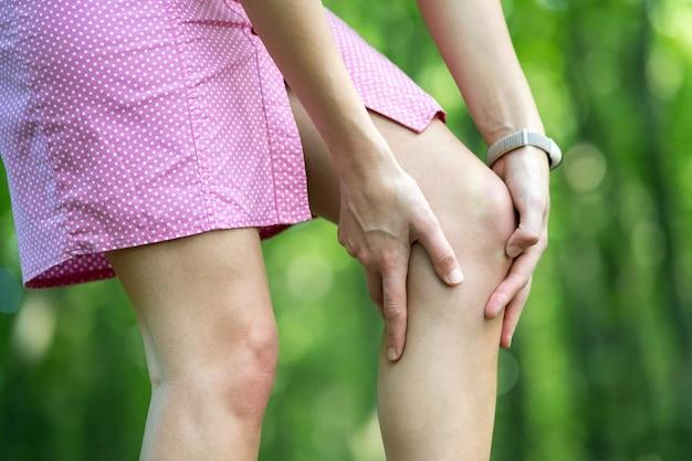 Женщина, держащая ее колено руками, болит в суставах.
