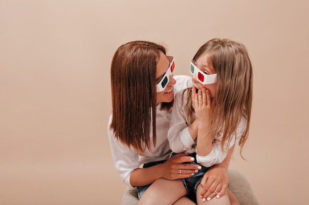 Woman holding her little charming girl and wearing glasses for cinema little girl watching movie with her mother