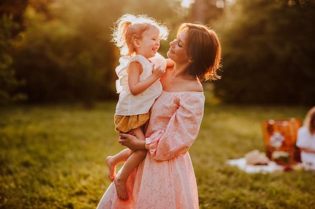 日当たりの良い夏の芝生で彼女の小さなかわいい娘を保持している女性。幸福。コピースペース。