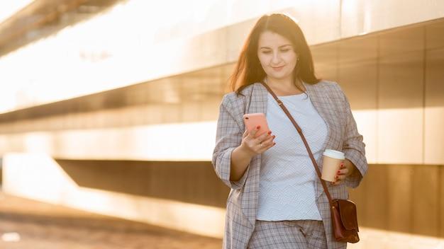 Женщина держит свой телефон на открытом воздухе с копией пространства