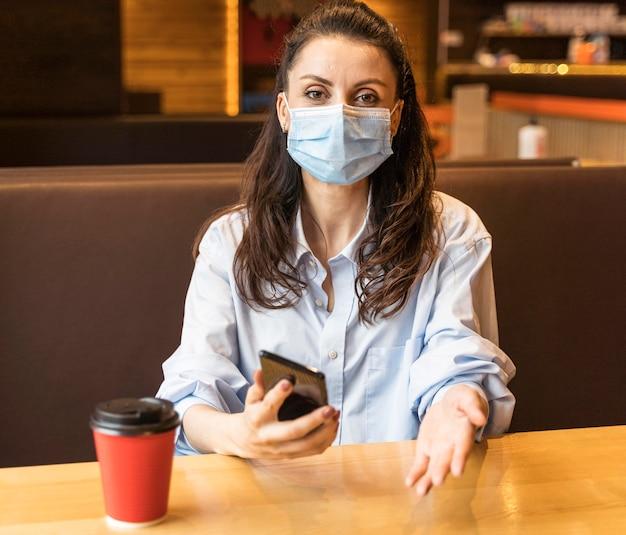 フェイスマスクを着用しながら携帯電話を持っている女性