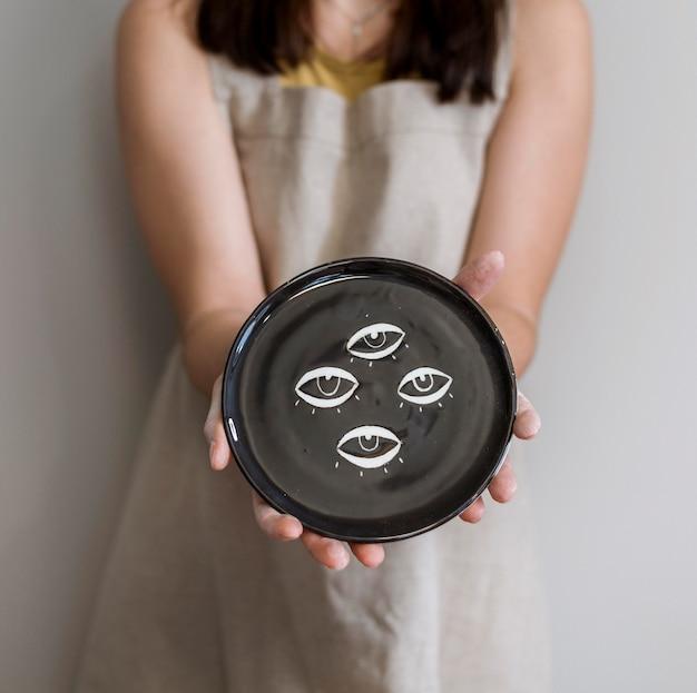Donna che mantiene le sue creazioni in ceramica