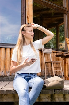 Woman holding her sunglasses and looking away