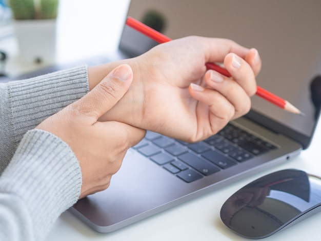 Woman holding her wrist pain from using computer long time
