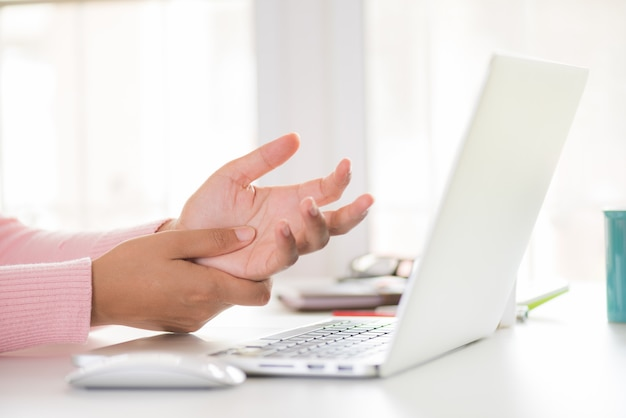 Woman holding her wrist pain from using computer. office syndrome by occupational disease.