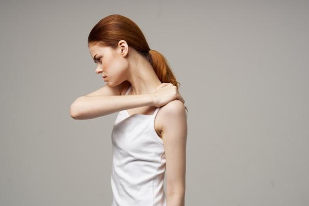 Женщина держит себя за плечи на бежевом фоне обрезанный вид