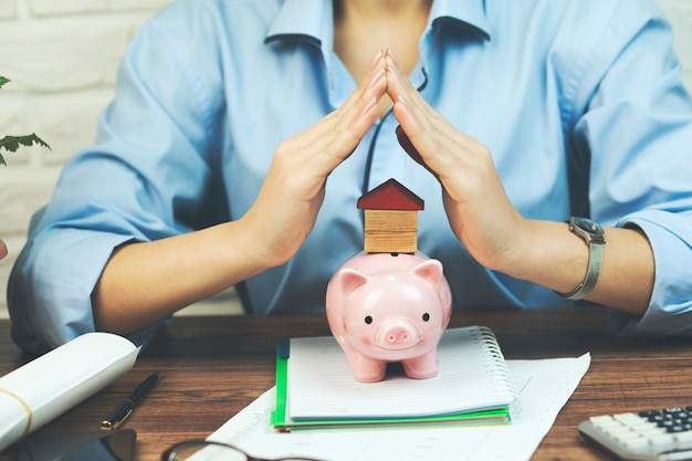 Woman holding home or house model and piggy bank