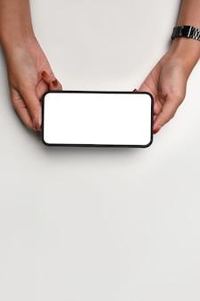 Женщина, держащая горизонтальный мобильный телефон на фоне ничуть.