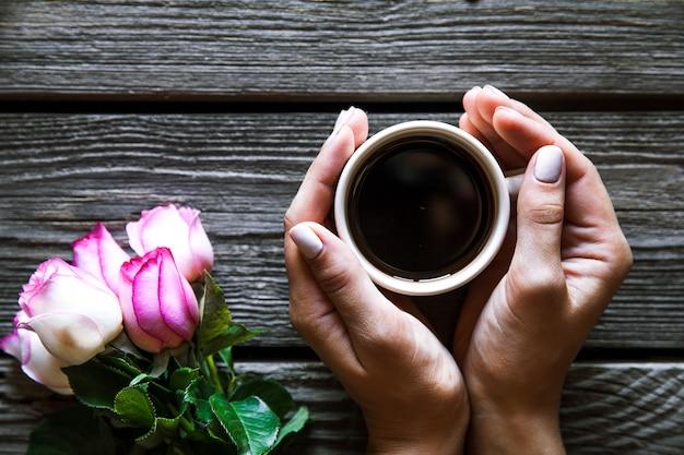 木製の背景に熱いコーヒーを保持している女性。朝、飲んで、休憩