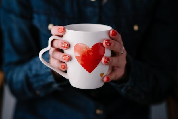 心でコーヒーの熱いカップを保持している女性