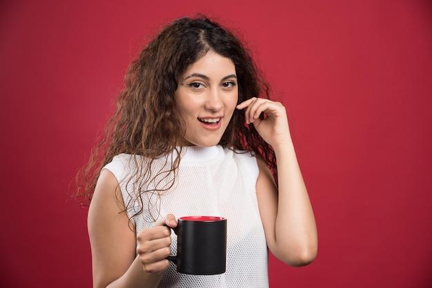 Donna che tiene una tazza calda e scura sul rosso