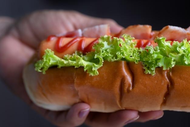 Woman holding hot dog