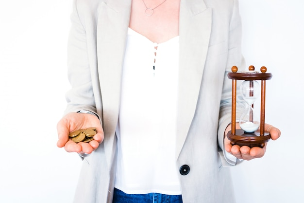 Woman holding hourglass and coins isolated on white background. time investment and retirement saving. urgency countdown timer for business deadline concept. time is money