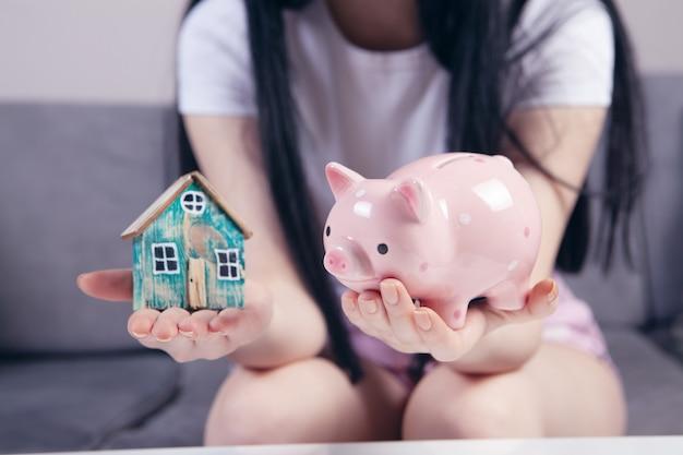 家と貯金箱を保持している女性