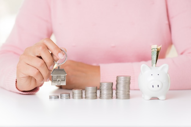 Woman holding house keychain with stack of coins and bank note dollar into piggy bank .