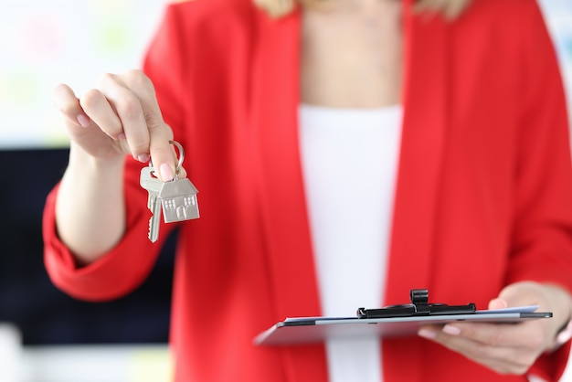 Woman holding house keys and clipboard with documents in her hands closeup real estate on