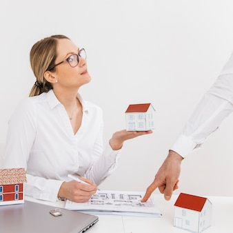 Woman holding house model looking at her colleague pointing on blue print over desk