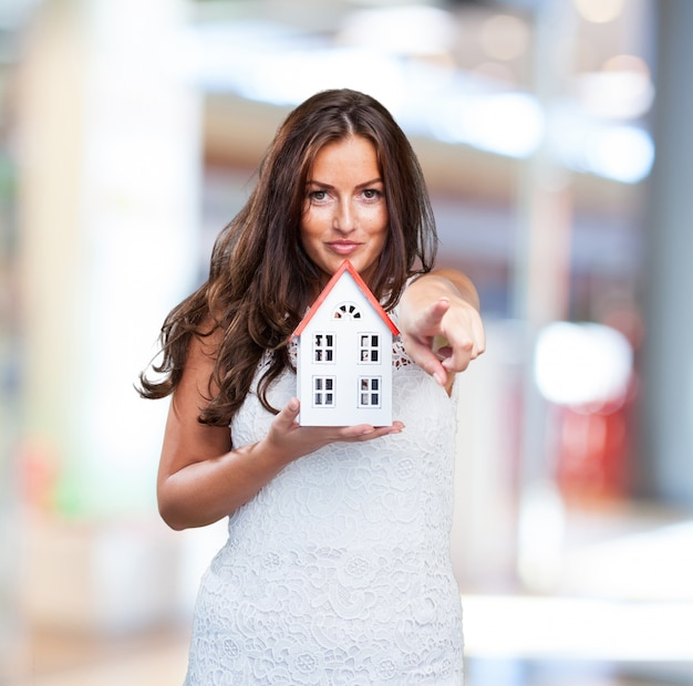 Woman holding a house and pointing to front