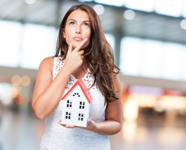 Woman holding a house and thinking about something