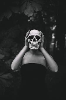 Woman holding human skull in forest