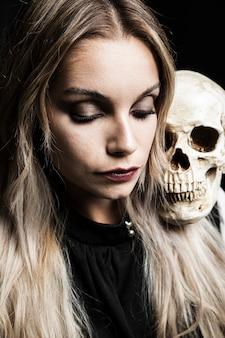 Woman holding human skull on shoulder