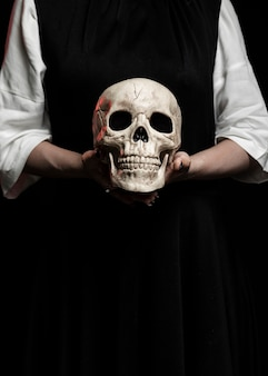 Woman holding human skull with copy space