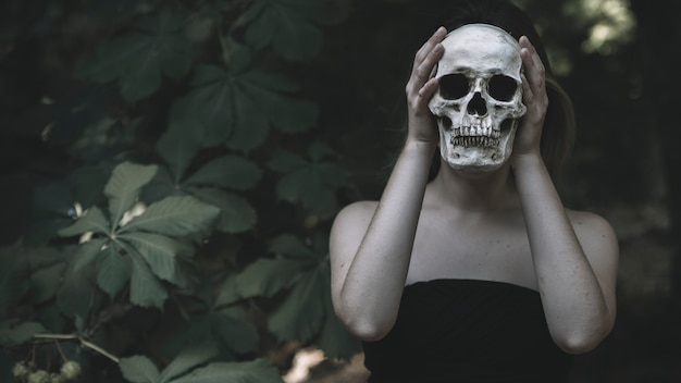 Woman holding human skull in woods daytime