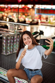 Woman holding ice cream taking selfie