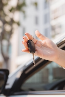 Woman holding the ignition keys of a car in her hand dangling them through the open side window