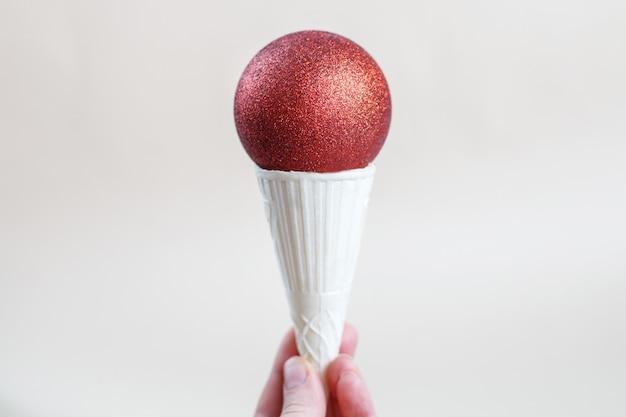 ベージュの背景に赤い光沢のあるクリスマスボールとアイスクリームコーンを手に持っている女性