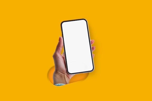 Женщина, держащая в руке смартфон с пустым экраном, изолированным на желтом фоне. концепция творческой технологии.
