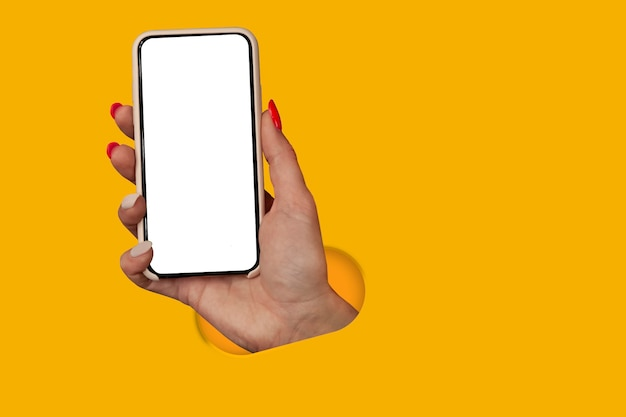 노란색 배경에 격리된 빈 화면이 있는 스마트폰을 손에 들고 있는 여자. 크리에이 티브 기술 개념입니다.