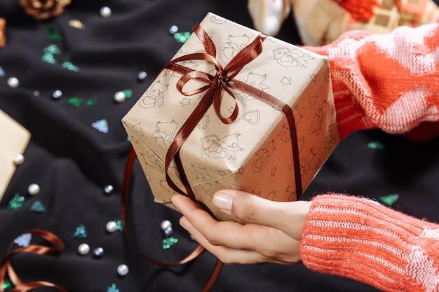 茶色のリボンでクリスマスプレゼントを手に持っている女性