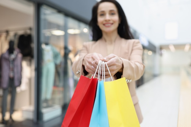 상점 근접 촬영에서 구매와 함께 많은 여러 가지 빛깔의 종이 가방을 손에 들고 여자