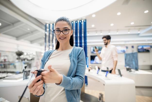 Женщина держит в руках часы, стоя в техническом магазине