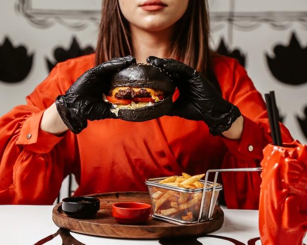 黒いパンとチーズバーガーを手に持った女性
