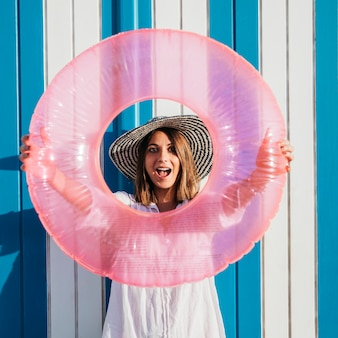 Woman holding inflatable ring around face