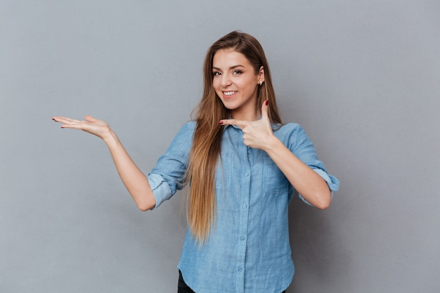 Woman holding invisible copyspace on the pound
