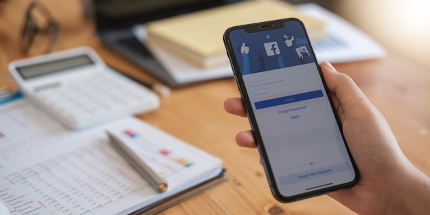 Woman holding a iphone x with social internet service facebook on the screen.