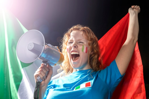 Donna che tiene la bandiera italiana e che parla nel megafono