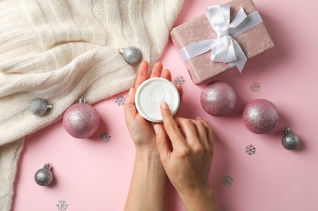 Woman holding jar of cream, warm sweater, gift boxes on pink, space for text. top view