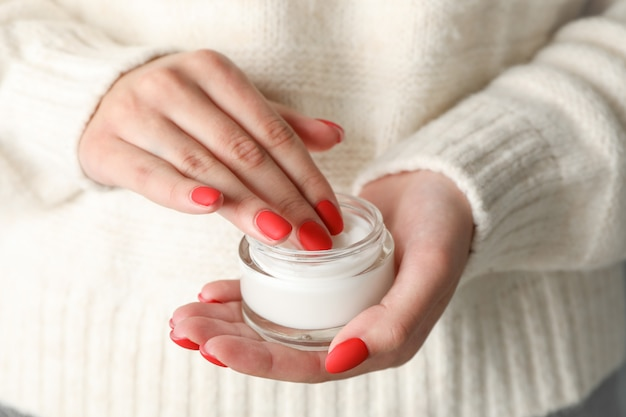 Woman holding jar of moisturizing cream, closeup. winter cosmetic. space for text