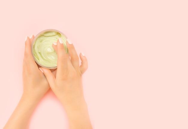 保湿クリームの瓶を持って、自宅で美容トリートメントをしている女性。アンチエイジングクリームの瓶は、美しいマニキュアを持つ女性の手に握られています。天然有機環境にやさしい
